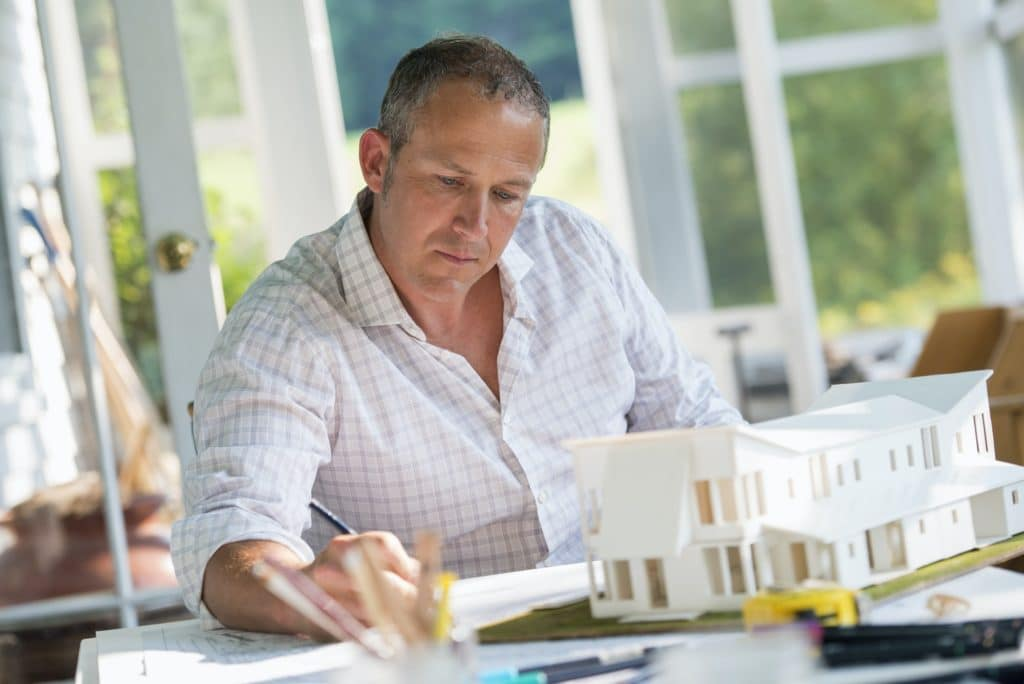 A man using a pencil drawing on an architect's plan, redesigning and renovation