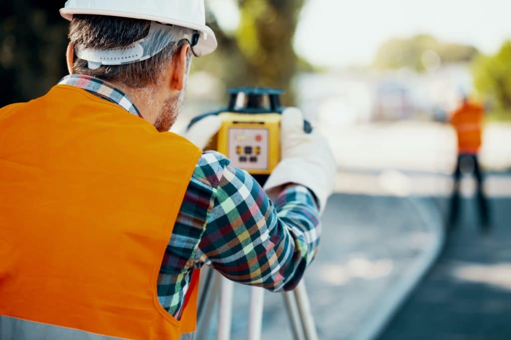 Geodesist in orange vest measuring with a total station