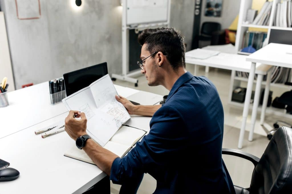 Stylish dark-haired architect in glasses and in a blue jacket is working with documents on the desk